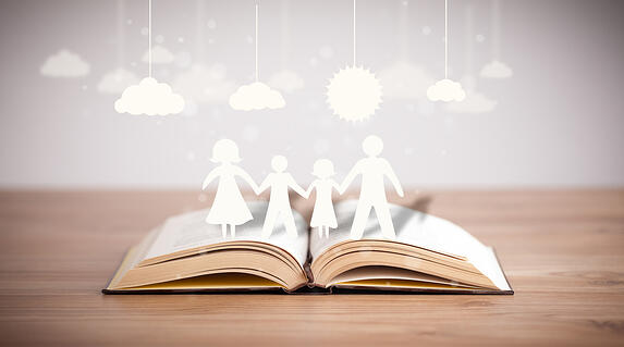Cardboard figures of the family on opened book. The symbol of unity and happiness-1